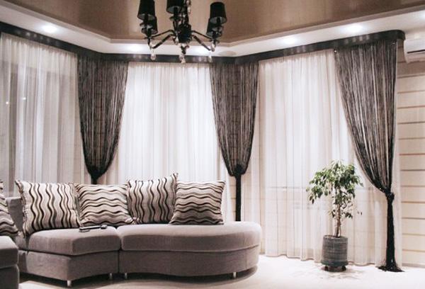 Светлые гардины в гостиной в сочетании с нитяными шторами