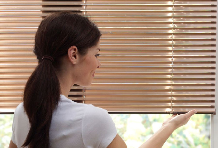 Девушка осматривает горизонтальные жалюзи