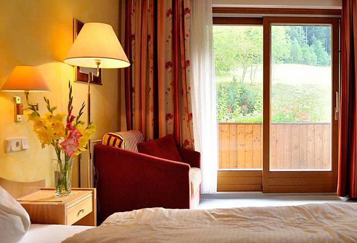 Желтые обои и красно-оранжевые шторы в спальне