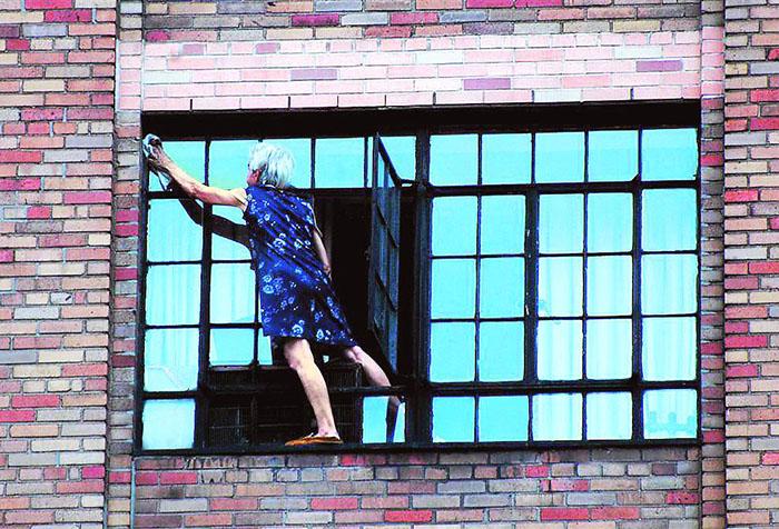 Пожилая женщина моет окно снаружи